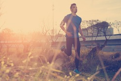 Handsome male athlete running in the park at sunset (little motion blur, intentional sun glare and vintage color)