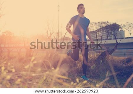 handsome male athlete running...