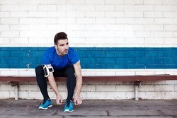 handsome male athlete sitting and tying shoelaces on the bench