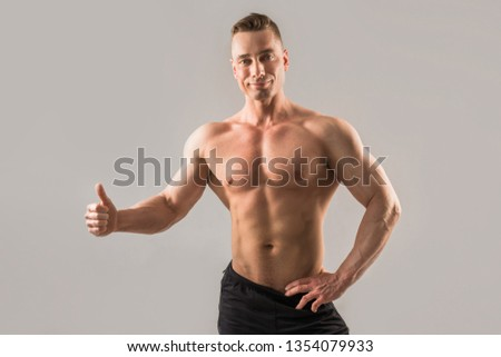 handsome male athlete with muscled muscles on gray background with hand gesture