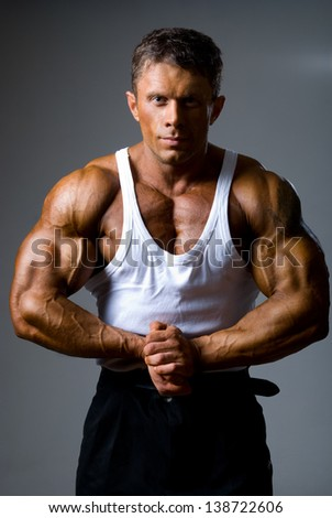 Handsome male bodybuilder is trained to pose with hands joined. Beautiful male body