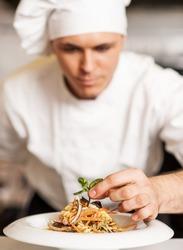 Handsome male chef dressed in white uniform decorating pasta salad.