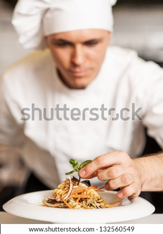 Handsome male chef dressed in white uniform decorating pasta salad.