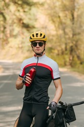 Handsome male cyclist standing with bicycle on forest road in autumn time with bottle of water in hands and posing on camera with serious face. Portrait of professional cyclist resting on training.