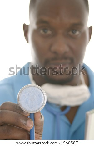 Handsome male doctor or nurse with a serious but calm expression holding a stethoscope toward the camera.  The model is out of focus; focus is on the end of the stethoscope.