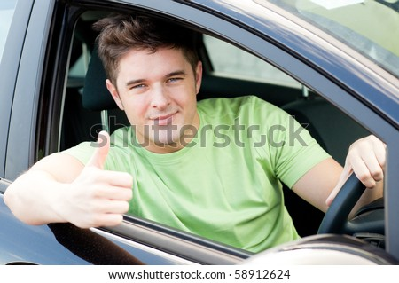 Handsome male driver sitting in a car and smiling