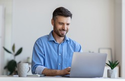 Handsome male entrepreneur working on laptop at desk in modern office, using computer at workplace, typing on keyboard, copy space