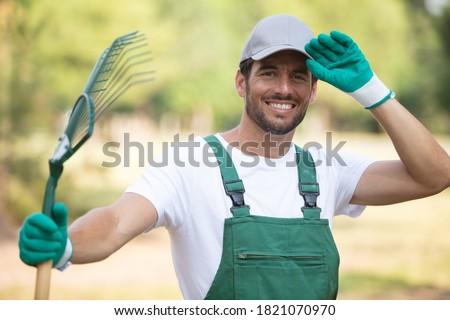 handsome male gardener holding a rake Photo stock ©