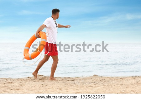 Handsome male lifeguard with life buoy at sandy beach Foto stock ©