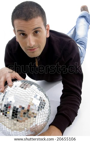 handsome male lying down on floor with a disco light ball on an isolated white background