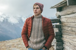 Handsome male model wearing warm sweater, winter coat and hat posing over mountains with snow. Active fashion clothes for cold weather.