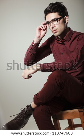 handsome male model with eye glasses dressed elegant posing in the studio looking serious