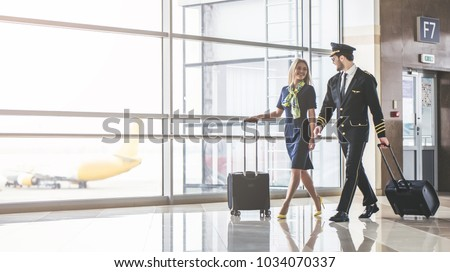Handsome male pilot and attractive female flight attendant are walking in airport terminal together. - Shutterstock ID 1034070337