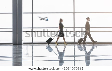 Handsome male pilot and attractive female flight attendant are walking in airport terminal together in front of panoramic wondows. - Shutterstock ID 1034070361