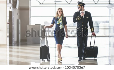 Handsome male pilot and attractive female flight attendant are walking in airport terminal together. - Shutterstock ID 1034070367