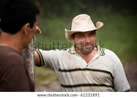 Handsome male ranch hands on dairy farm in Costa Rica