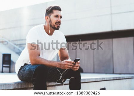 Handsome male runner dressed in stylish apparel looking away while listening audio advices for training connected to 4g internet on cellphone, man in sportswear sitting on urban setting with phone
