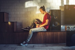 Handsome man, a music lover listens to music with headphones with mobile phone in a modern interior against the media and large speakers. Enjoying music is fun and communicates on the Internet at home