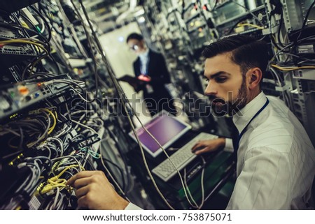 Handsome man and attractive woman are working in data centre. IT engineer specialists in network server room. Running diagnostics and maintenance. Technicians examining servers.
