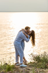 handsome man and attractive woman kissing near lake