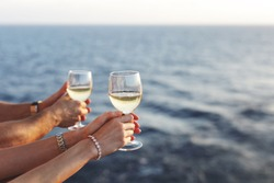 handsome man and beautiful woman standing with glasses white wine on cruise ship in Caribbean sea at nice sunset  background
