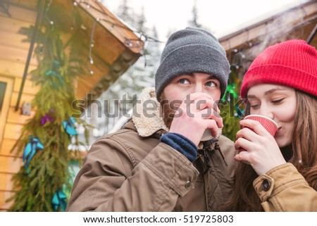 Handsome man and pretty young woman drinking hot coffee on traditional christmas market