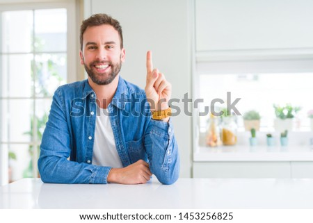 Handsome man at home showing and pointing up with finger number one while smiling confident and happy.