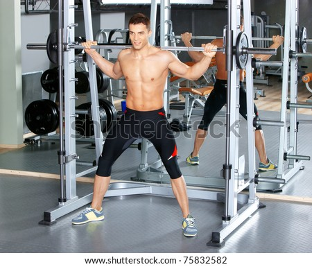 Handsome man at the gym doing exercises - stock photo