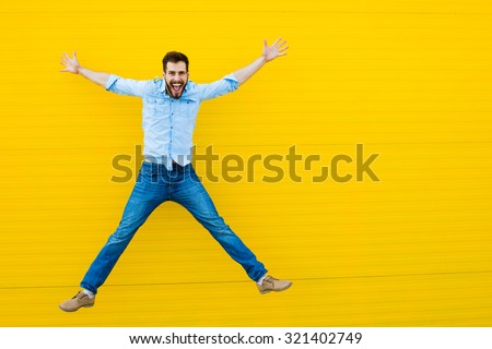 handsome man casual dressed celebrating and jumping on yellow background #321402749