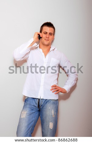 Handsome man casually leaning against gray wall while talking on the phone