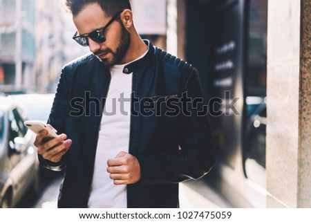 Handsome man checking mail on smartphone using application while spending time on city street,cropped image of male in trendy outfit sending text messages via cellphone chatting in networks outdoors #1027475059