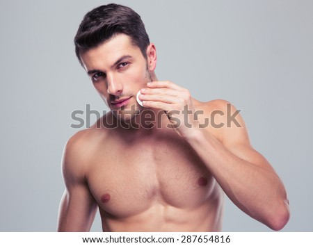 Handsome man cleaning face skin with batting cotton pads over gray background and looking at camera