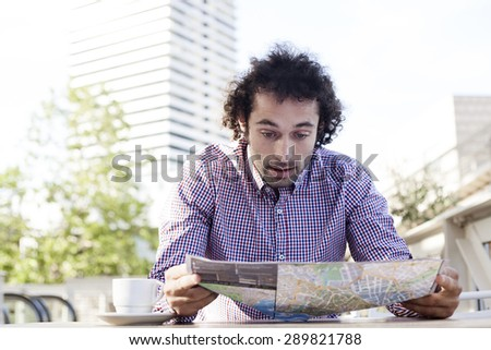 Handsome man consulting a guide in a restaurant terrace. Vacation concept.