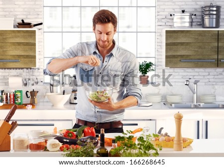 Handsome man cooking at home preparing salad in kitchen.