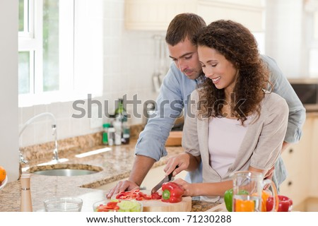 Handsome man cooking with his girlfriend at home - stock photo