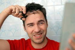 Handsome man cutting his own hair with a scissors and looks in the mirror. self-care in the conditions of global quarantine and closed hairdressers and beauty salons. trim your bangs. stay at home
