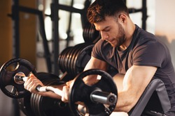 Handsome man doing biceps lifting barbell on bench in a gym