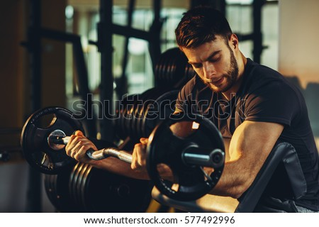 Handsome man doing biceps lifting barbell on bench in a gym #577492996