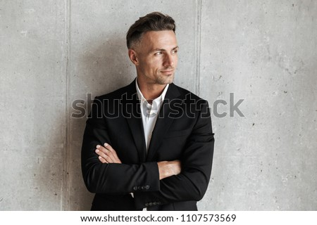 Handsome man dressed in suit holding arms folded and looking away over gray wall background
