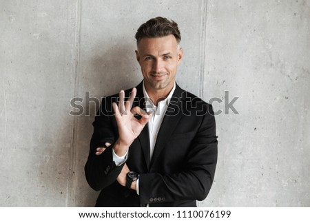 Handsome man dressed in suit showing ok gesture over gray wall background