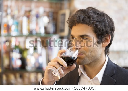 Handsome man drinking a glass of red wine in bar Stockfoto ©