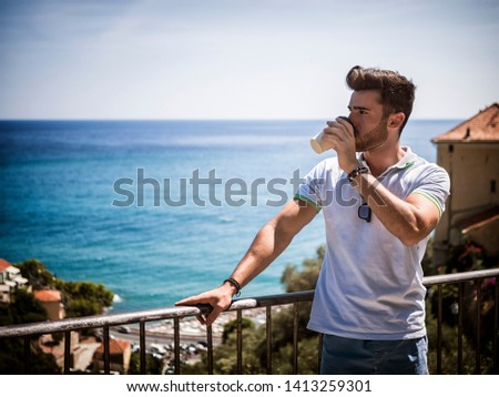 Handsome man drinking american coffee from big paper cup, outdoor standing by handrail in Italian sea town in a summer day. Horizontal outdoors shot