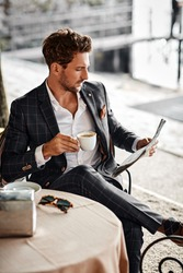 Handsome man drinking coffee and reading newspaper in cafe
