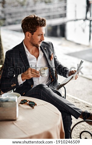 Handsome man drinking coffee and reading newspaper in cafe Foto stock ©