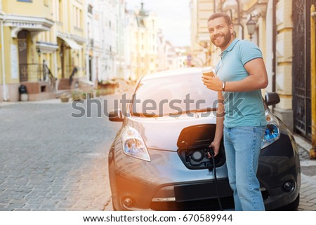 Handsome man drinking coffee while charging electric car #670589944