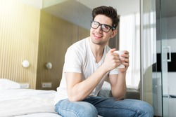 Handsome man drinking morning coffee in the bed