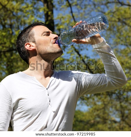 handsome man drinking water in a park
