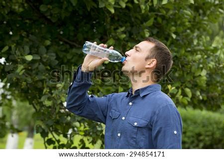 Handsome man drinking water in summer park