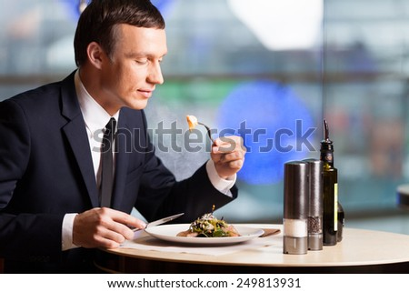 Handsome man eating at restaurant inside. side view of man sitting on chair in cafe and eating food