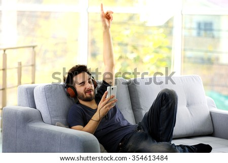 Handsome man emotionally listens music with headphones on grey sofa in the room